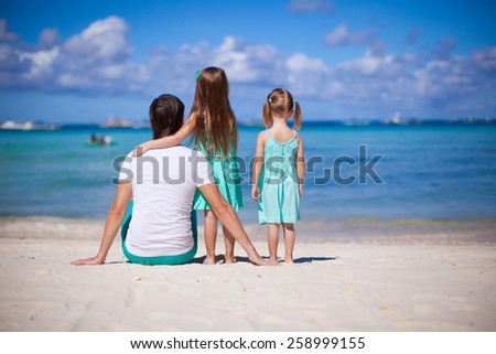 Happy family of two girls and young dad on white beach during summer vacation - stock photo