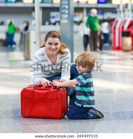 Happy family of two: Mother and little son at the airport, traveling together. - stock photo