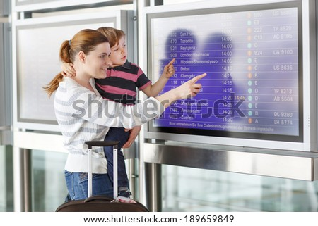 Happy family of two: Mother and little son at the international airport, looking on flight board at terminal, going on vacation. - stock photo