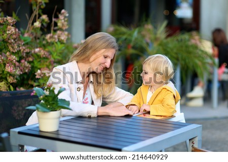 Happy family of two, mother, attractive young woman and her daughter, adorable toddler girl  enjoying lunch at a beautiful outside cafe choosing meal from menu card - stock photo