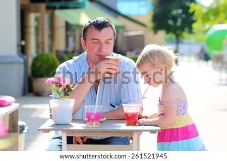 Happy family of two, smiling man with his cute toddler daughter, relaxing together in summer outdoors cafe drinking coffee, juice or smoothie and eating muffin - father and child, parenting concept - stock photo