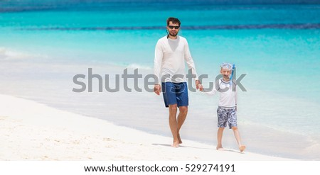 happy family of two walking at perfect caribbean white sand beach with turquoise lagoon at anguilla island