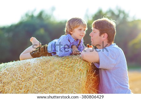 Happy family of two: Young father and his little son having fun on yellow hay field in summer. Funny kid boy and young man enjoying summertime - stock photo