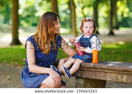 Happy family of two:  young mother and adorable baby daughter playing together in summer park and having fun together, outdoors. - stock photo