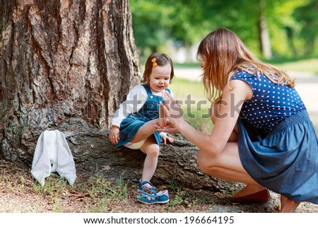 Happy family of two: young mother and cute toddler girl in summer park and having fun together, outdoors.