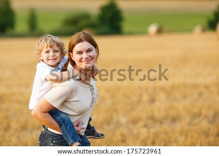 Happy family of two: Young mother and little toddler boy walking on yellow hay field in summer - stock photo