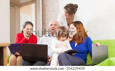 Happy family of with various portable computers on sofa at home - stock photo