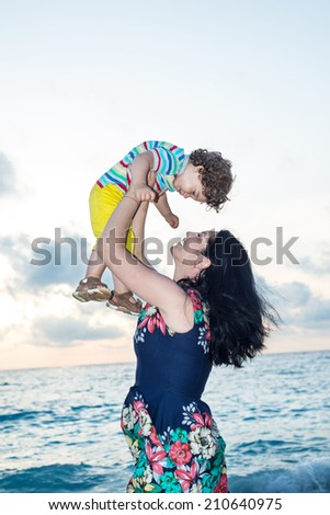 Happy family  ogf mother and toddler at ionian sea in dusk - stock photo