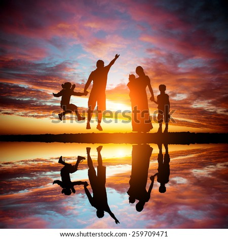 happy family on a background of the magnificent sunset over the sea - stock photo