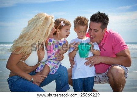 Happy family on a beach looking at new findings. - stock photo