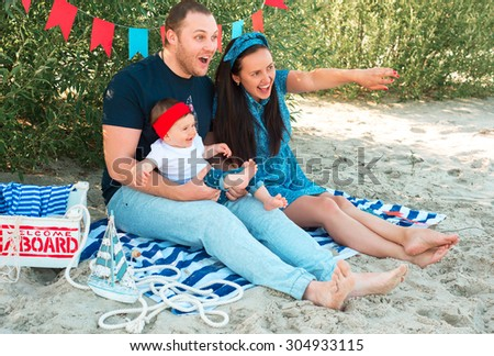 happy family on a beach. mother shows something to her baby - stock photo