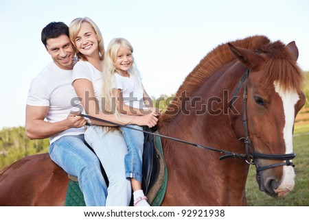 Happy family on a horse - stock photo