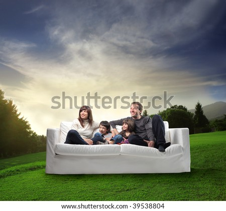 happy family on a sofa in a beautiful natural landscape - stock photo