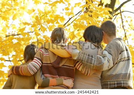 Happy family on a walk during the fall in the park,back view - stock photo