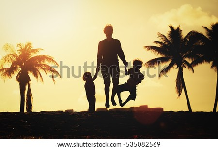 happy family on beach - father with kids jumping from joy at sunset