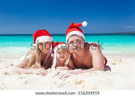 Happy family on beach in Santa hats, mother, father and little daughter. - stock photo