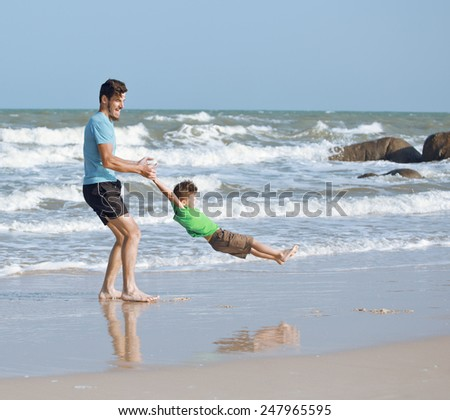happy family on beach playing, father with son walking sea coast, rocks behind