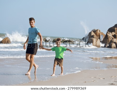 happy family on beach playing, father with son walking sea coast, rocks behind smiling enjoy summer warm