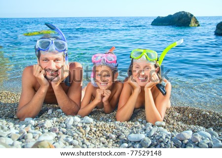 Happy family on beach with snorkles ready to have a good time swimming - stock photo