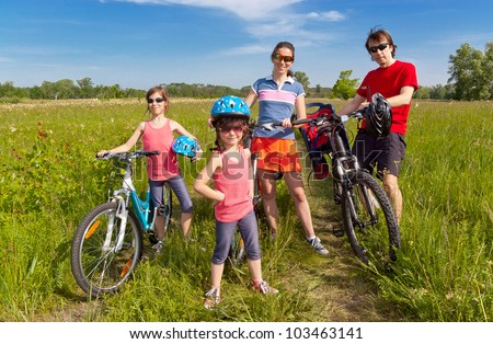 Happy family on bikes, cycling outdoors. Active parents and kids on bicycles. Family sport and fun, healthy lifestyle concept - stock photo