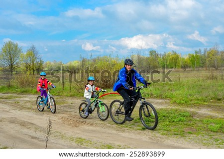 Happy family on bikes, father cycling with kids outdoors, active family sport
