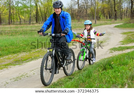 Happy family on bikes, father cycling with kids outdoors, active family sport  - stock photo