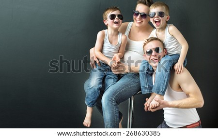 Happy family on black studio background - stock photo