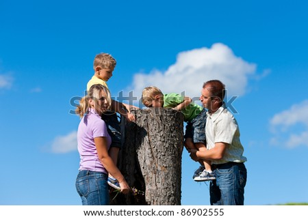 Happy family on excursion in summer - they discovered a trunk