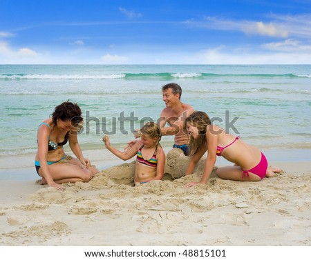 happy family on holidays playing at the beach, throwing sand at each other - stock photo