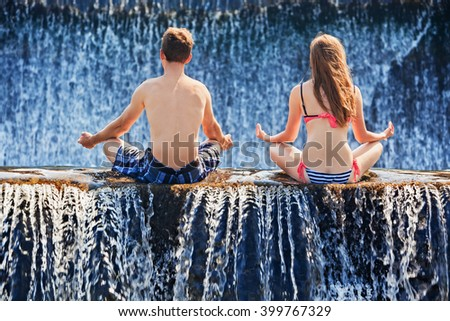 Happy family on honeymoon holidays - just married couple in yoga lotus position after swimming in waterfall pool. Active lifestyle, people outdoor travel activity on summer vacation on tropical Bali. - stock photo