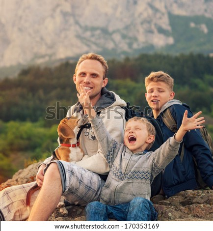 Happy family on mountain walk. Father with sons and pet - stock photo