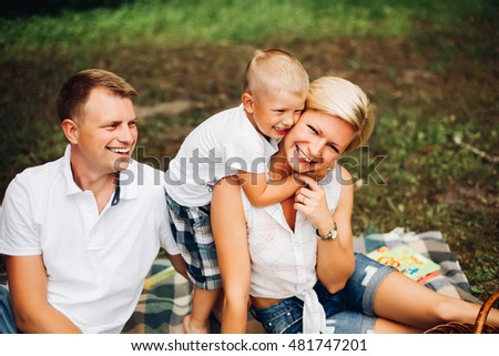 Happy family on picnic, a good Sunny day, talking, laughing, talking. Dressed in the same style, the concept of happiness, luck, family