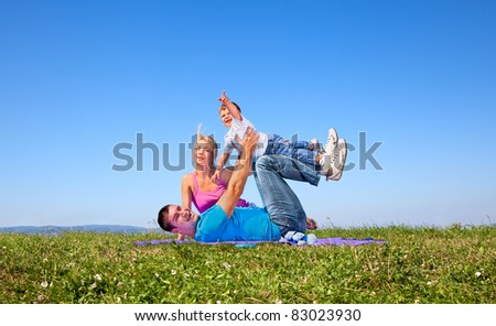 Happy family on picnic in park under blue sky - stock photo