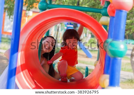 Happy family on playground in summer