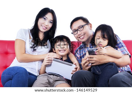 Happy family on red sofa looking at camera with white background - stock photo