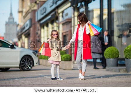 Happy family on shopping outdoors. Mother and daugher make purchases on their shopping and have fun walking on street outdoor. - stock photo