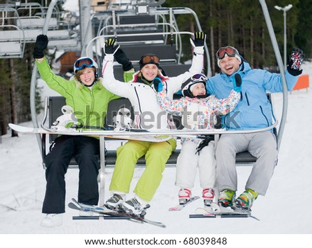 Happy family on ski lift - stock photo