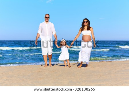 Happy family on the beach sand walking pregnant mother woman - stock photo