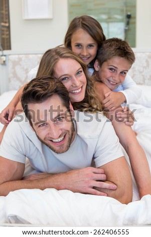 Happy family on the bed at home in bedroom - stock photo