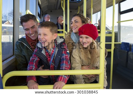 Happy family on the bus. The children are sitting on the knees of their parents and looking out the window. They are all laughing and smiling. - stock photo