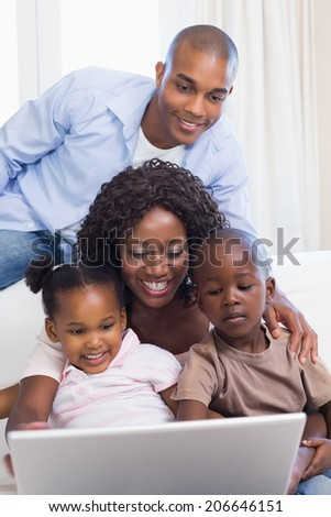 Happy family on the couch together using laptop at home in the living room