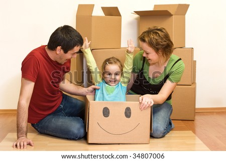 Happy family on the floor of their new home with lots of cardboard boxes, unpacking - stock photo