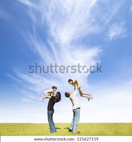 happy family on the grass with cloud background - stock photo