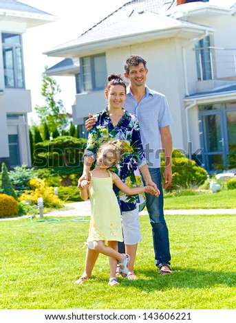 Happy family on the lawn in front of his new cottage - stock photo