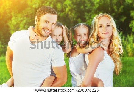 happy family on the nature of the summer, mother, father and children twin sisters - stock photo