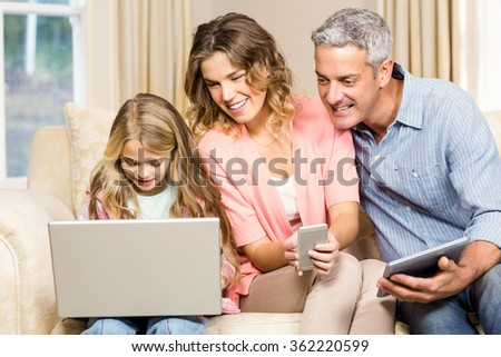 Happy family on the sofa looking at laptop screen