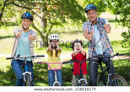 Happy family on their bike with thumbs up at the park on a sunny day - stock photo