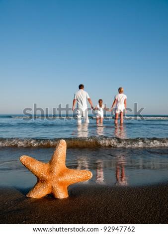Happy family on tropical beach - stock photo
