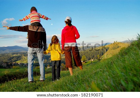 Happy family on vacation in mountains, hiking and looking and beautiful view  - stock photo