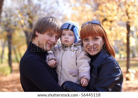 Happy family on walk in park in the autumn - stock photo